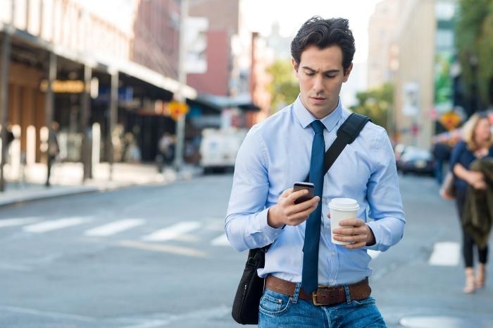 Homem andando na rua e mexendo no celular