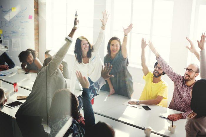 Equipe em reunião comemorando resultados com gamificação