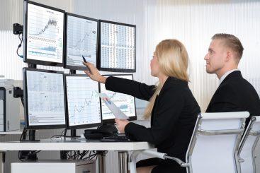 Colaboradores analisando gráficos por meio de painel gerencial