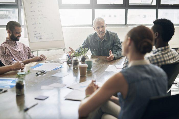 Equipe de trabalho em reunião com seu líder em sala de reunião