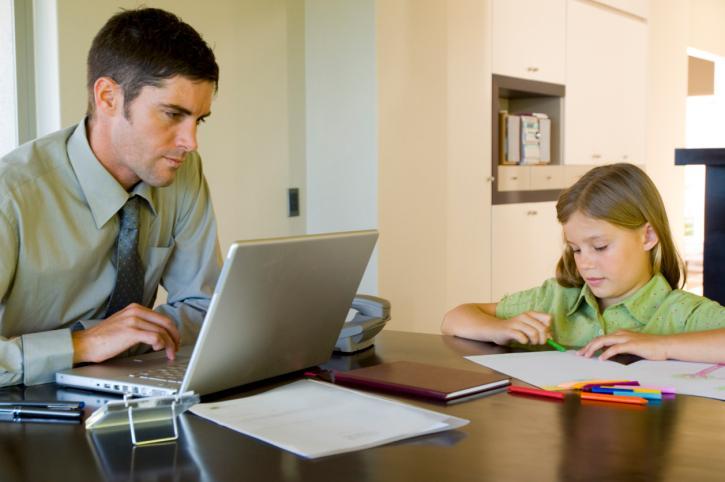 Pai trabalhando com criança ao lado