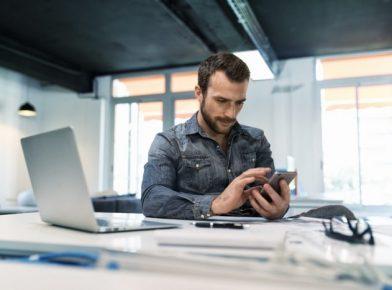 uso das redes sociais no trabalho homem com celular na mão