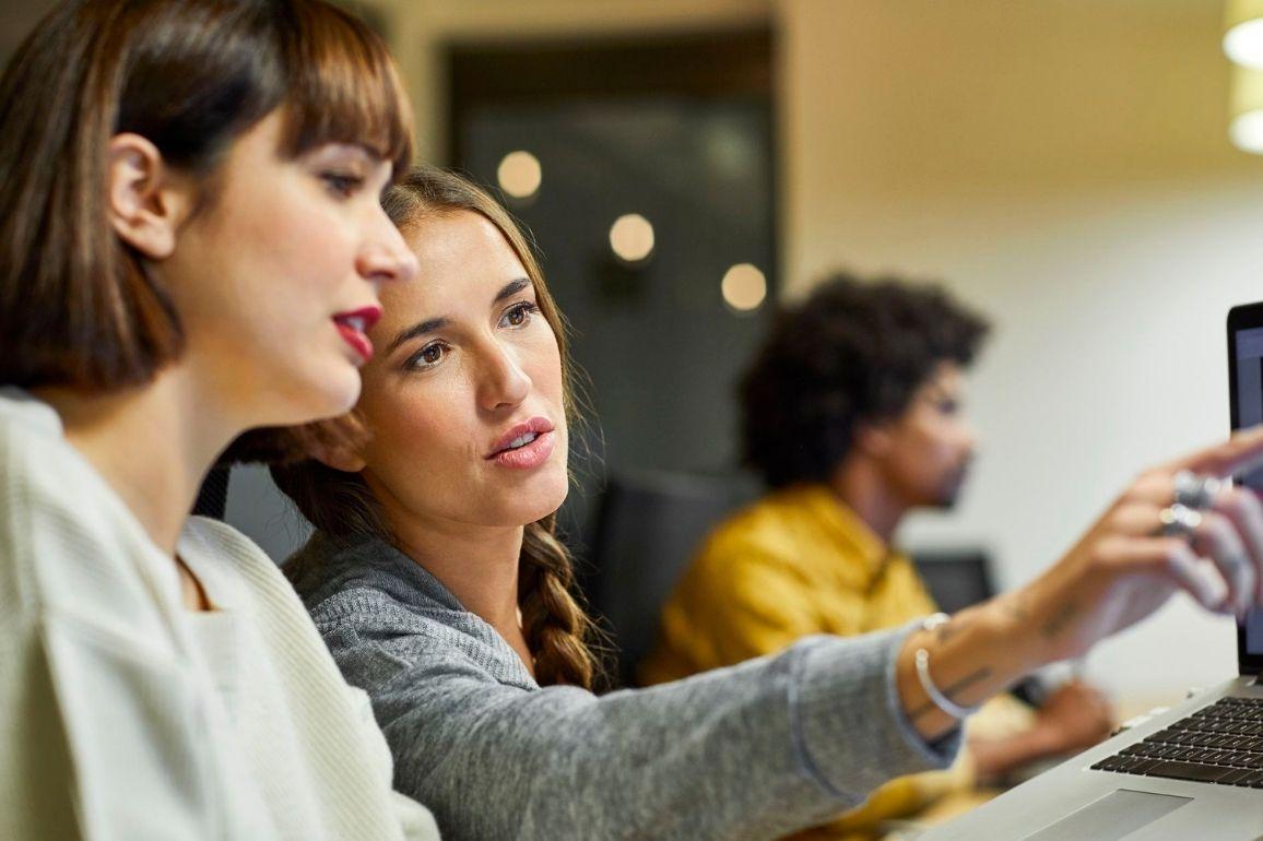 duas mulheres conversando olhando para o computador